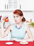 Woman choosing between healthy food and cake Stock Photography