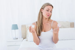 Woman choosing her medicine on bed Stock Image