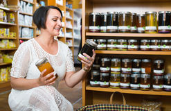 Woman choosing honey from assortment in drugstore Royalty Free Stock Images