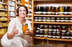 Woman choosing honey in store Stock Image
