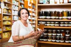 Woman choosing honey in store Stock Photo