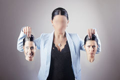 Woman choosing identity. Young business woman holding her smile face in one and her grumpy face mask in the other hand confused with which identity to choose Stock Image