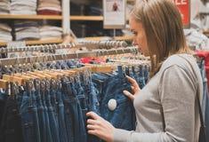 Woman choosing jeans. Woman choosing jeans in clothing store royalty free stock photo