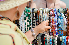 Woman choosing jewelry in row of necklaces and bracelets Royalty Free Stock Photo