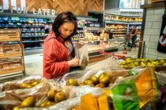Woman choosing kiwi fruit at supermarket royalty free stock photo