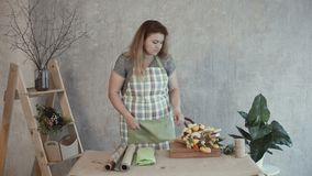 Woman choosing kraft paper for edible arrangement. Attractive woman in apron choosing wrapping paper for edible bouquet arrangement at workplace. Creative stock footage