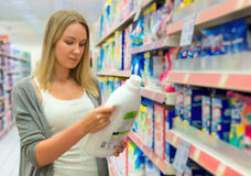 Woman choosing laundry detergent. Royalty Free Stock Photos