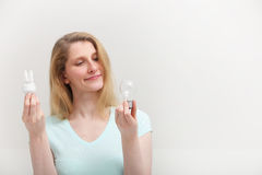 Woman choosing a light bulb Royalty Free Stock Photos