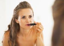 Woman choosing lipstick in bathroom Stock Photo