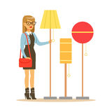 Woman Choosing A Living Room Lamp, Smiling Shopper In Furniture Shop Shopping For House Decor Elements. Cartoon Character Looking For Home Interior Design Royalty Free Stock Photo