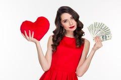 Woman choosing between love or money stock image