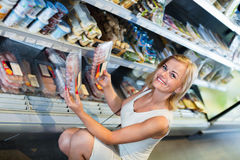 Woman choosing meat in refrigerated section in food store. Smiling happy young woman choosing meat in refrigerated section in food store Stock Images