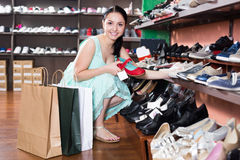 Woman is choosing modern red sandals in shoes shop. Young smiling woman is choosing modern red sandals in shoes shop Royalty Free Stock Photos