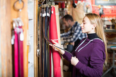 Woman choosing new belt in leather workshop Royalty Free Stock Images