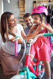 Woman choosing new bicycle and helmet for little girl in bike shop. Woman choosing new bicycle and helmet for happy little girl in bike shop royalty free stock images