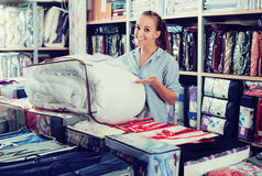 Woman choosing new coverlet Royalty Free Stock Photo