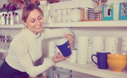 Woman choosing new crockery in dinnerware store Royalty Free Stock Image