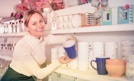 Woman choosing new crockery in dinnerware store Stock Photos