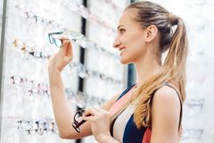 Woman choosing new glasses out of shelf in optician store stock image
