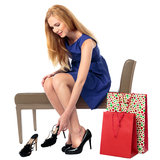 Woman choosing a new pair of shoes. Beautiful elegant young woman choosing a new pair of shoes sitting on a seat in a store trying on a stylish pair of stilettos Stock Images