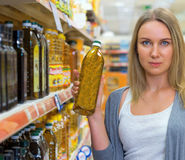 Woman choosing olive oil. Royalty Free Stock Photo