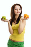 Woman choosing between orange and green apple Royalty Free Stock Photos