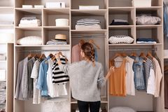 Woman choosing outfit from large wardrobe closet with stylish clothes