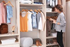 Woman choosing outfit from large wardrobe closet with stylish clothes. Shoes and home stuff stock photos