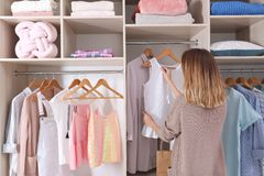 Woman choosing outfit from large wardrobe closet with stylish clothes. And home stuff stock photography