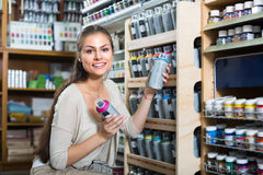 Woman choosing paint in aerosol can in shop Stock Photos