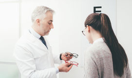 Woman choosing a pair of glasses stock photography
