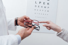 Woman choosing a pair of glasses. After the eye exam, the optician is giving her an advice Royalty Free Stock Photo