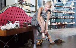 Woman  choosing on pair of  shoes in fashion store Royalty Free Stock Images