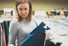 Woman choosing pants. Woman choosing pants in clothing store Stock Photo