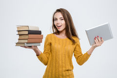 Woman choosing between paper books or tablet computer Royalty Free Stock Image