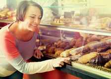 Woman choosing pastry in cafe showcase. Happy smiling brunette woman gladly choosing pastry in cafeteria store window Stock Photography