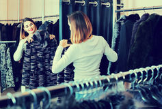 Woman choosing patterned fur jacket in women's cloths store Stock Photography