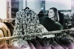 Woman choosing patterned fur jacket in women's cloths store Stock Photo