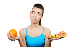 Woman choosing between pizza and orange Royalty Free Stock Image