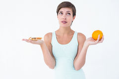 Woman choosing between pizza and an orange Stock Images