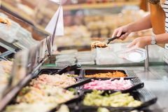 Woman choosing prepared meal. In grocery store Stock Photos