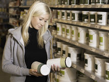 Woman choosing between products in hardware store. Woman deciding between products in a DIY hardware store Stock Image