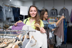 Woman choosing pullover in shop. Smiling young longhaired girl choosing pullover in shop Stock Photos