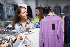 Woman choosing pullover in shop. Smiling young longhaired women choosing pullover in shop Royalty Free Stock Images