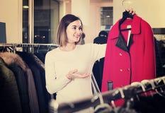 Woman choosing red woolen coat in women's cloths store Royalty Free Stock Photos