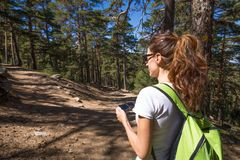 Woman choosing the right path in the forest. Hiking woman with white shirt and green backpack looking at smartphone to choose the right way, between two paths in Stock Photography