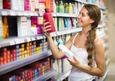 Woman choosing shampoo at store Stock Photography