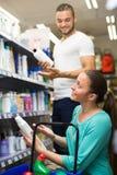 Woman choosing shampoo at store Royalty Free Stock Photos