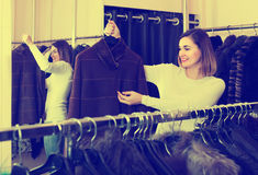 Woman choosing sheepskin coat in women's cloths store Stock Image