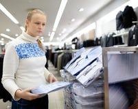 Woman is choosing shirt for man. Royalty Free Stock Photos